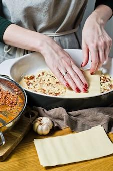 El chef cocina lasaña italiana casera.