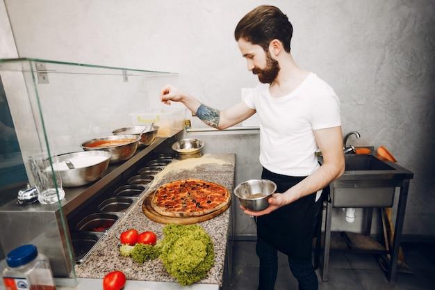 Chef en la cocina prepara pizza.
