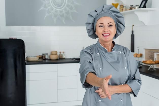 Chef en cocina preparado para estrecharle la mano