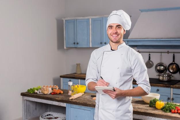 Chef en cocina tomando notas