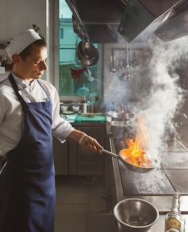 Chef cocinando carne en la cocina del restaurante o del hotel