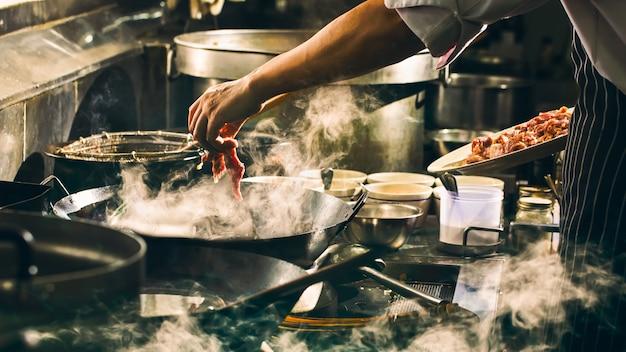 Chef está cocinando carne en wok