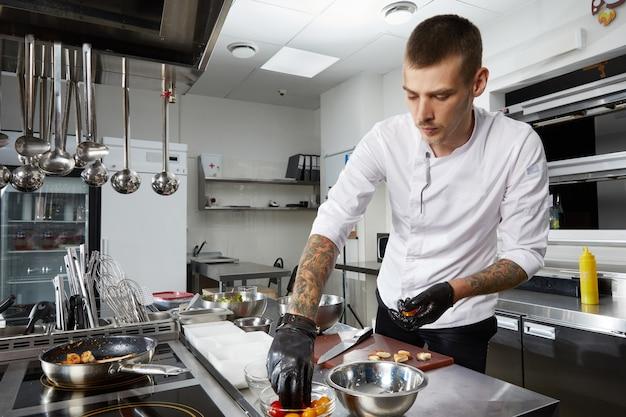 Chef cocinando en la cocina moderna en el restaurante del hotel preparando ensalada de camarones