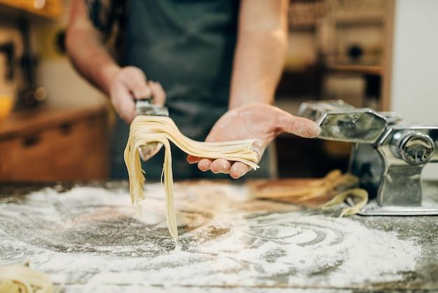 Chef cocinando fettuccine en máquina de pasta