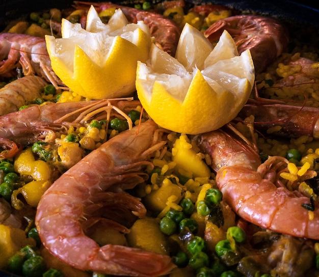 Chef cocinando una paella burbujeante con gambas, limón y mariscos variados. preparación de tapas típicas de deliciosa comida española. plato sabroso de españa