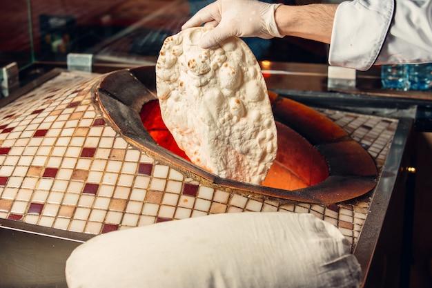 Chef cocinando pan lavash dentro del horno tandir.