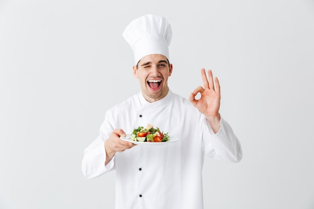 Chef cocinero hombre emocionado vistiendo uniforme mostrando ensalada verde fresca en un plato aislado sobre la pared blanca, ok