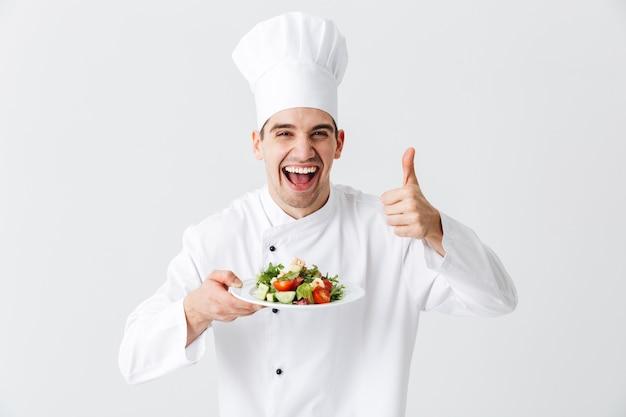 Chef cocinero hombre emocionado vistiendo uniforme mostrando ensalada verde fresca en un plato aislado sobre la pared blanca