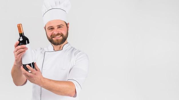 Chef cocinero mostrando botella de vino