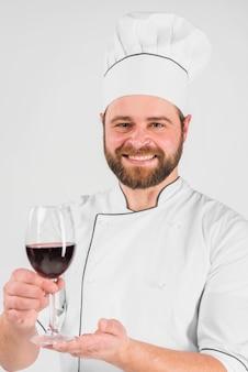 Chef cocinero sonriendo y sosteniendo una copa de vino