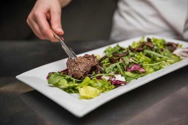 Chef colocando carne de res en ensalada