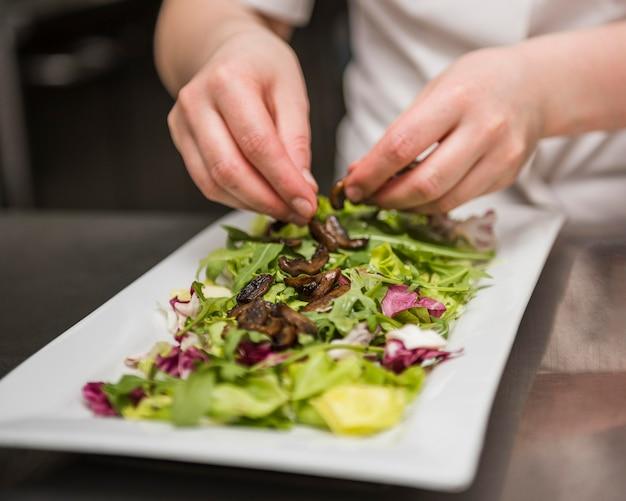 Chef colocando champiñones en ensalada