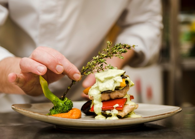 Chef colocando hierba en comida gourmet