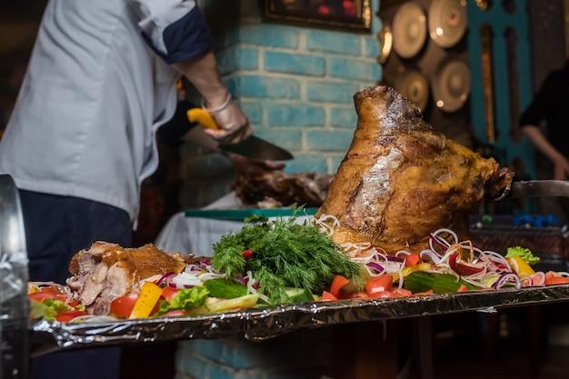 Chef corta carne de cerdo al horno en un restaurante