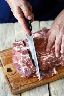 El chef corta la carne cruda en el tablero.