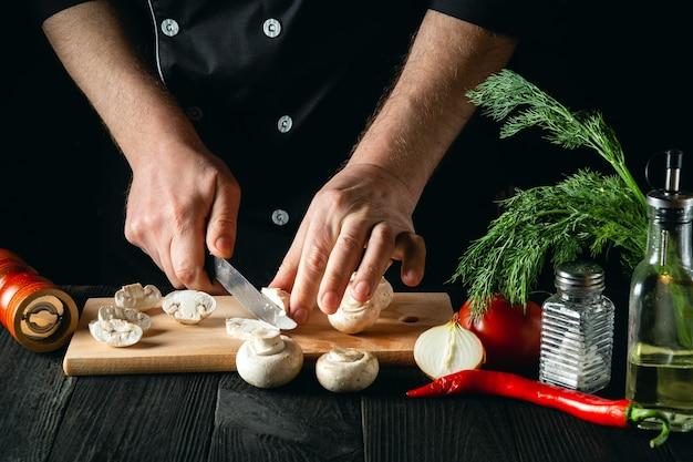El chef corta champiñones con un cuchillo para preparar una deliciosa comida.