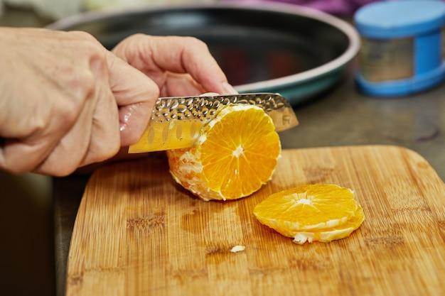 El chef corta la naranja en rodajas con un cuchillo. de cerca