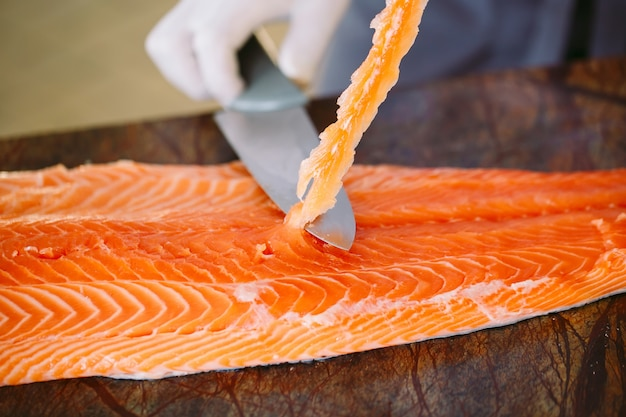 El chef corta el salmón sobre la mesa.