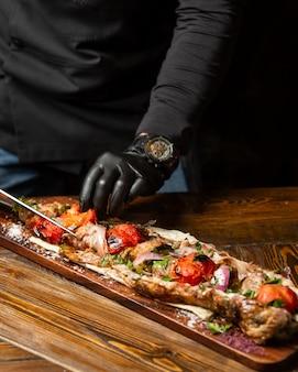 El chef corta tomates, carne en una baqueta con cebolla y hierbas en pan de pita.