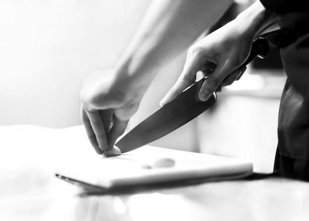 El chef corta las verduras que se cocinan en la cocina, las manos cortando verduras, preparando verduras