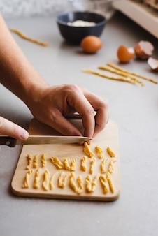 Chef cortando masa en trozos pequeños