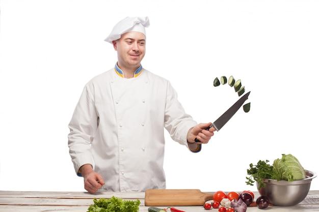 Chef cortando un pepino verde en su cocina