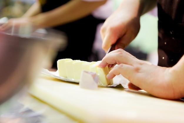 Chef, corte, mantequilla, en, cocina, corte, mantequilla, con, un, cuchillo, en, primer plano