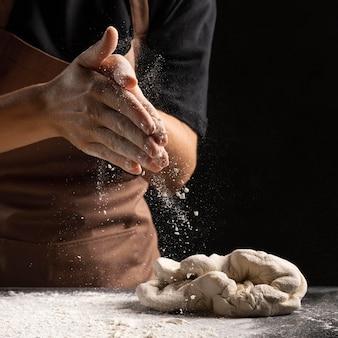 Chef cubriendo las manos con flout para amasar la masa