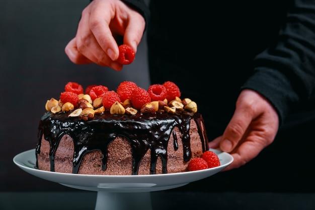 Chef decorar el pastel de chocolate de bayas frescas silvestres.