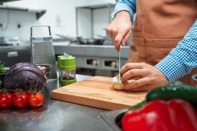 El chef en delantal marrón cocinando en la cocina de un restaurante