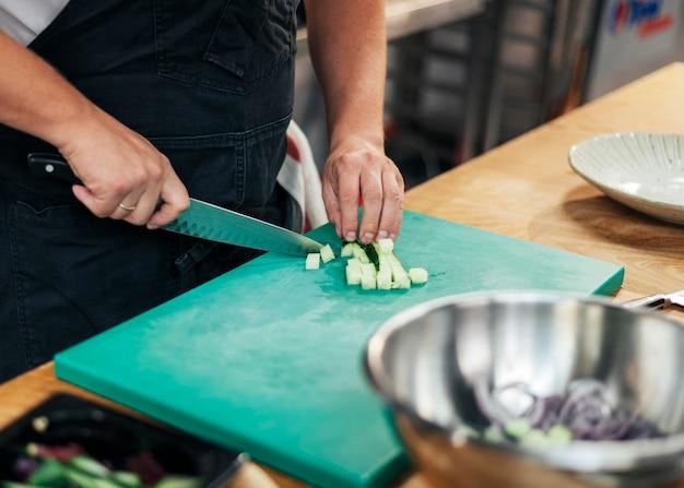 Chef con delantal para picar pepino en la cocina