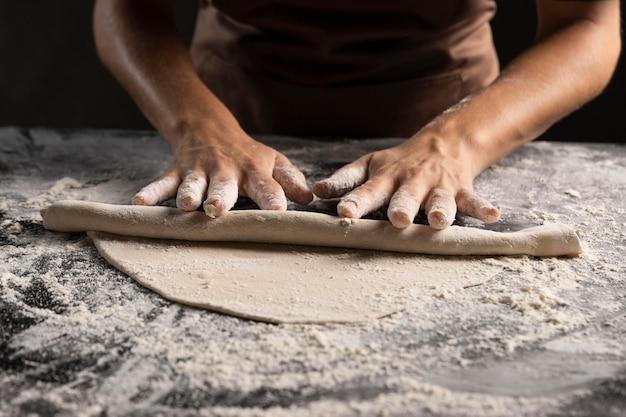 Chef enrollando masa con mucha harina sobre la mesa