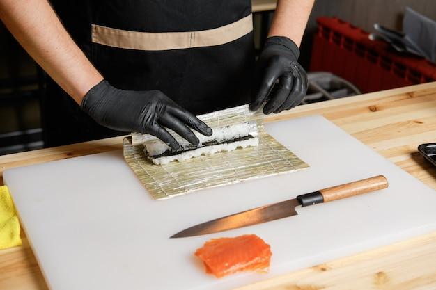 Chef envolviendo rollos de salmón