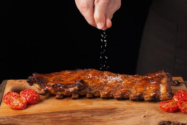 El chef espolvorea sal en costillas de cerdo listas para comer.