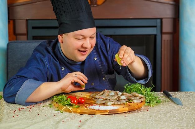 Chef exprime jugo de limón en camarones tigre. retrato. foto divertida.