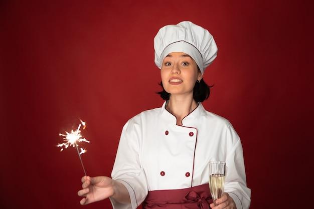 Chef femenina celebrando con copa de champán y bengalas encendidas