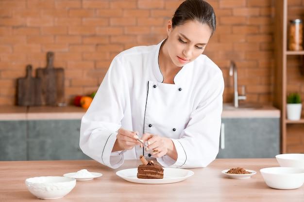 Chef femenina decorar un sabroso postre en la cocina