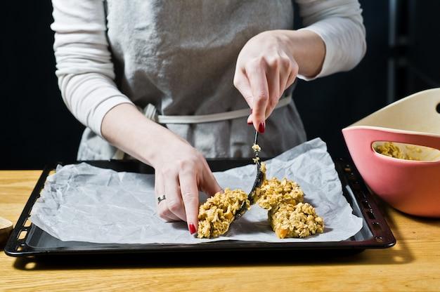 Chef femenina preparando galletas de avena, extendió la masa en las bandejas.