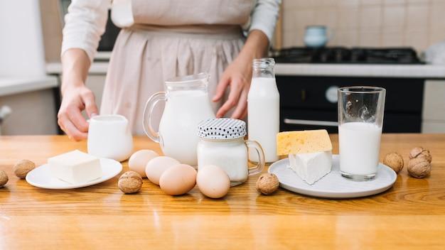 Chef femenina con queso; huevos; nogal y leche en mesa de madera para preparar pastel.