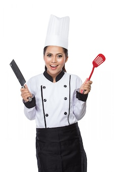Chef femenina en un tradicional sombrero y abrigo, con cuchillo y espátula