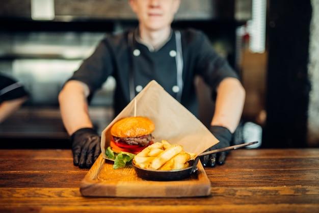 Chef en guantes contra jugosa hamburguesa con bistec fresco. una verdadera hamburguesa cocinando, preparación de alimentos en la cocina, carne a la parrilla