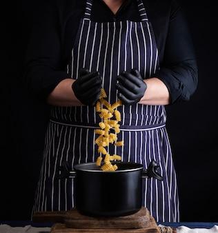 Chef con guantes de látex negro, delantal a rayas vierte pasta cruda fusilli en una sartén de metal