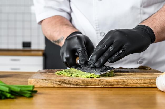 Un chef con guantes negros prepara guacamole con aguacate fresco hass.