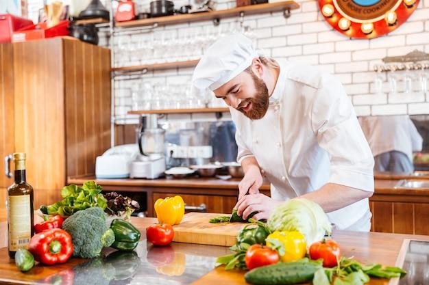 Chef guapo alegre haciendo ensalada de verduras en la cocina