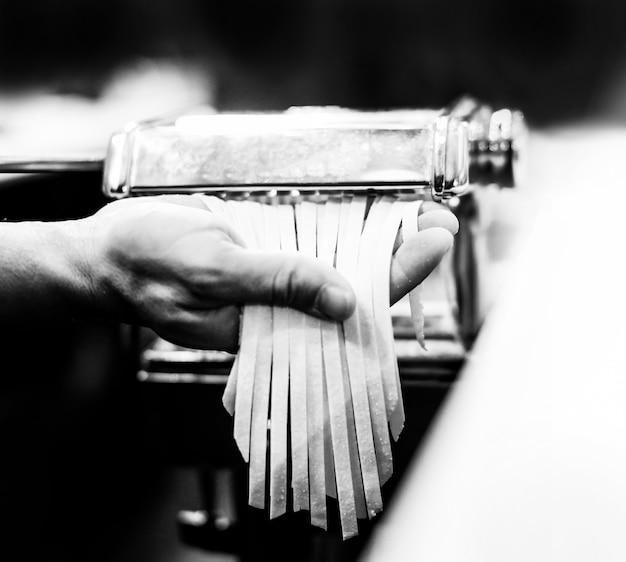 Chef haciendo pasta con una máquina, pasta fresca casera