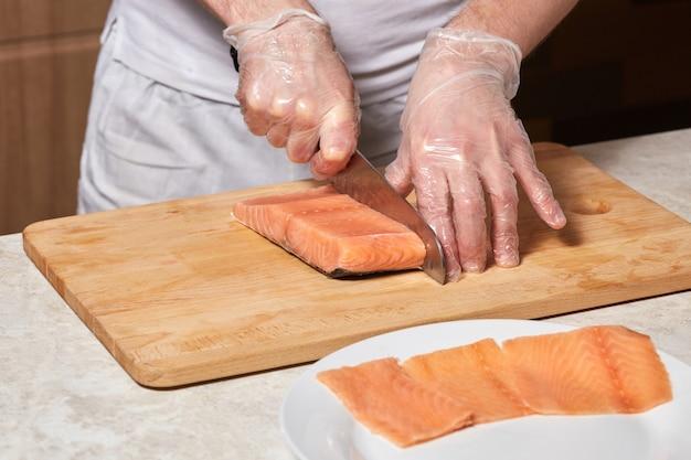 Chef haciendo rollos de sushi. cortar salmón pescado en tablero de madera