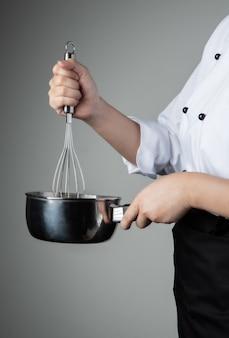 Chef con herramienta para batir ingredientes de mezcla de alimentos de repostería