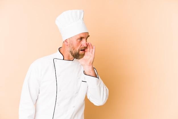 Chef hombre en la pared de color beige está diciendo una noticia secreta de frenado caliente y mirando a un lado