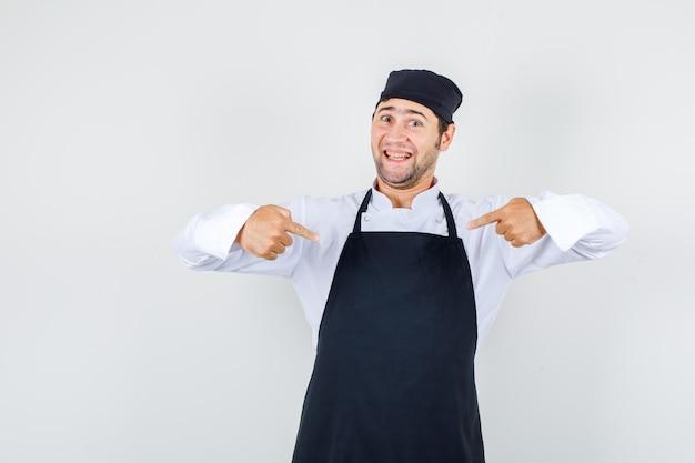 Chef hombre señalando con el dedo a sí mismo en uniforme, delantal y mirando confiado, vista frontal.
