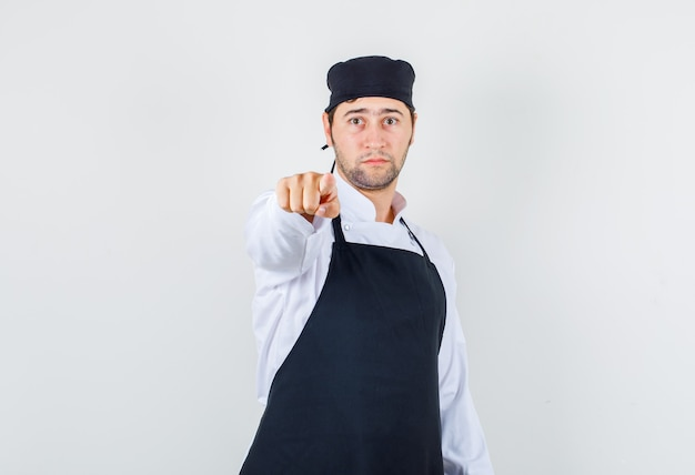 Chef hombre señalando con el dedo en uniforme, delantal y mirando serio, vista frontal.